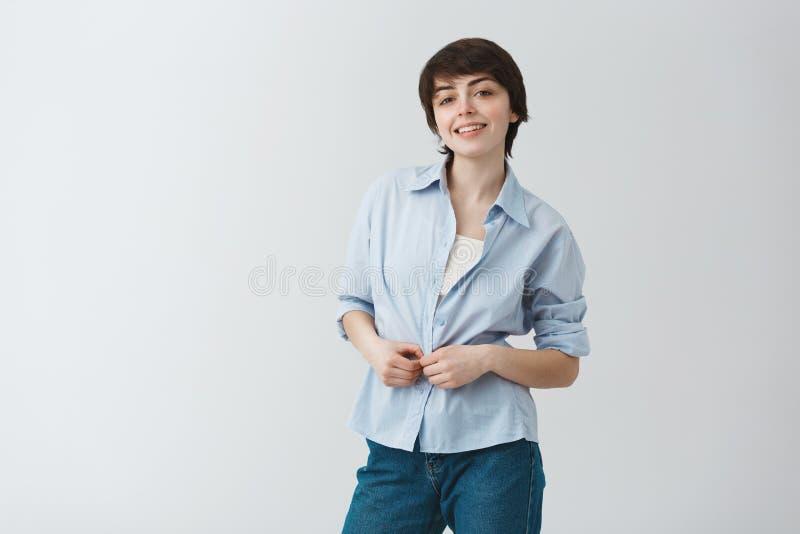 Gullig ung kvinnlig student med kort mörkt hår som ler, knäppas upp skjortan och in camera ser brightfully med lyckligt fotografering för bildbyråer