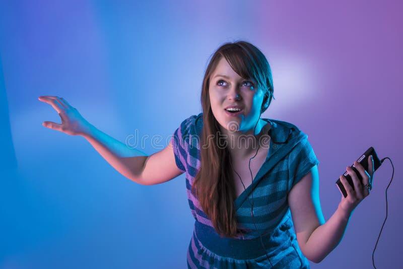 Gullig ung kvinnlig utfrågningmusik från en spelare mp3 royaltyfri fotografi