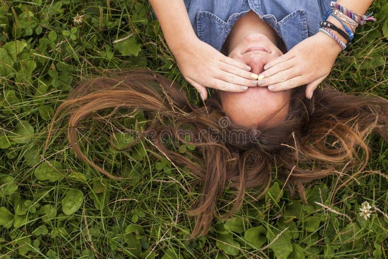 Gullig ung långhårig flicka för närbild som ligger på det gröna gräset royaltyfri foto