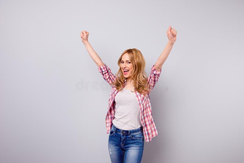 Gullig ung le kvinna i jeans och rutigt triumfera för skjorta arkivfoto