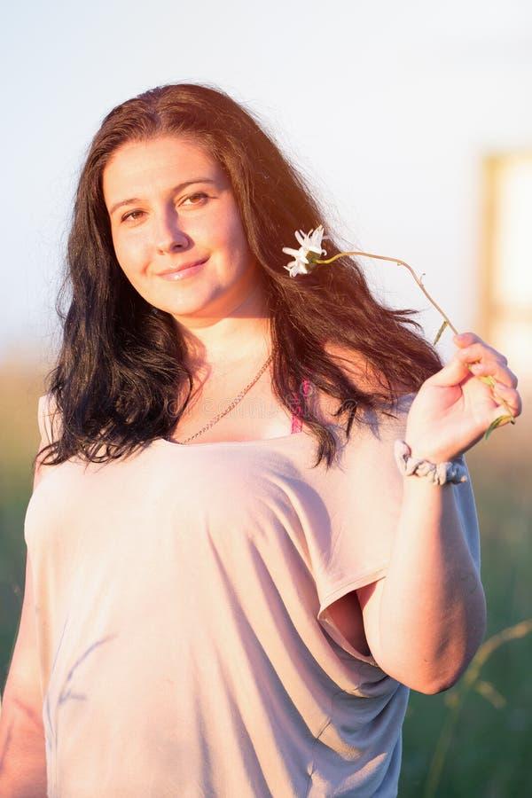 Gullig ung le kvinnastående med kamomillblomman under sommarsolnedgång utomhus arkivfoto