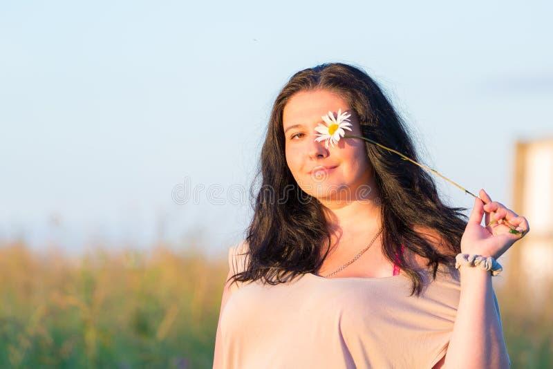 Gullig ung le kvinnastående med kamomilltusenskönablomman under sommarsolnedgång utomhus royaltyfri bild