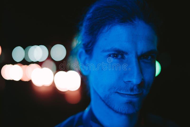 Gullig ung man med ett skägg på hans framsida som faller blått ljus royaltyfri foto