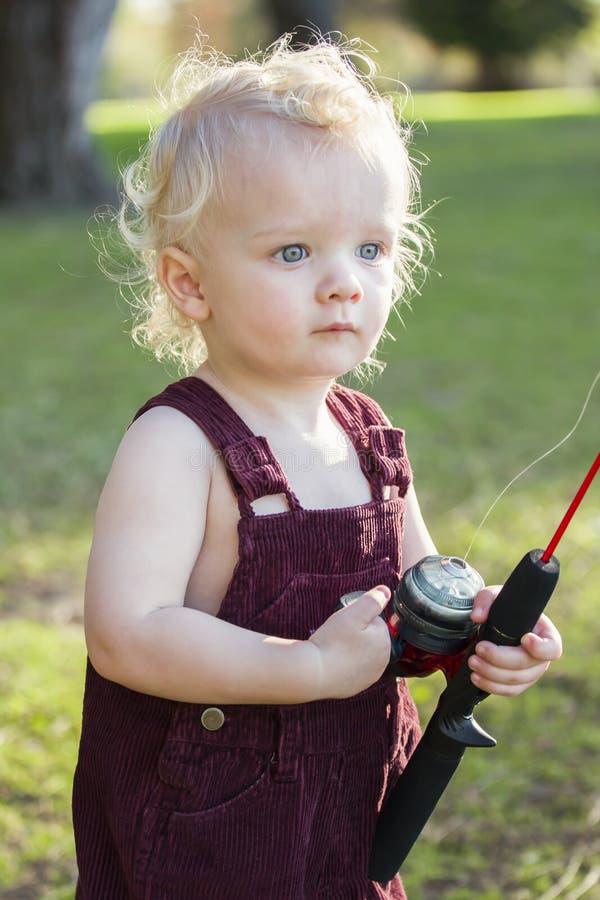 Gullig ung pojke med fiske Pole på sjön royaltyfri fotografi