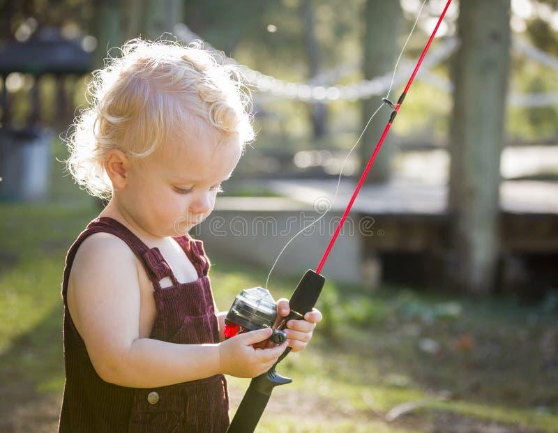 Gullig ung pojke med fiske Pole på sjön arkivfoto