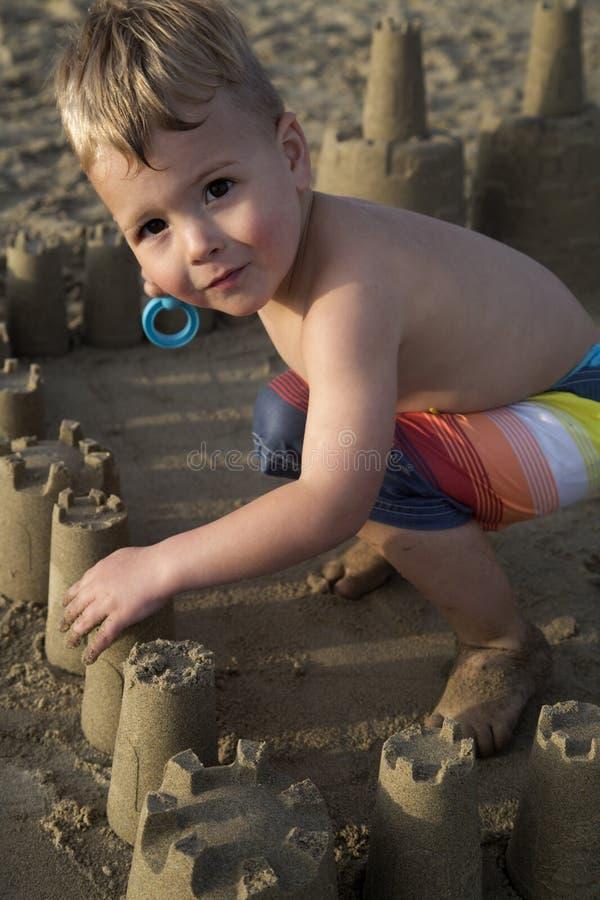 Gullig ung pojke som bygger en strandsandslott royaltyfria bilder