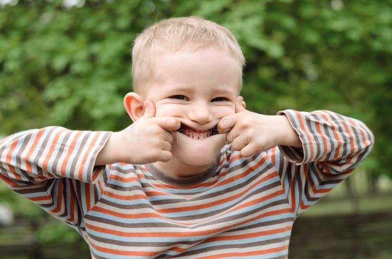 Gullig ung pojke som drar ett roligt uttryck royaltyfri fotografi