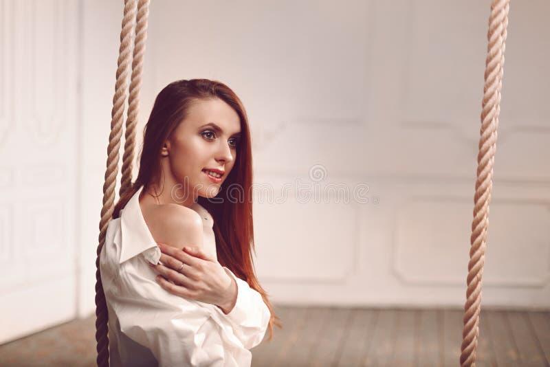 Gullig ung rödhårig mankvinna med långt hårsammanträde på gunga i skjorta för man` s arkivbild