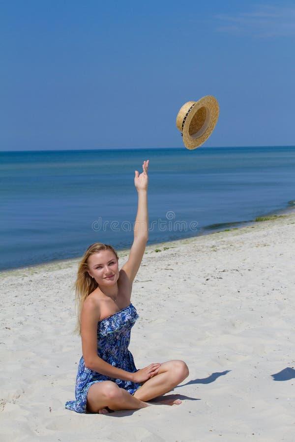 Gullig ung sexig flicka med en hatt, i blåttklänningsammanträde på stranden, havsbakgrund Frihets- och gyckelbegrepp royaltyfri foto