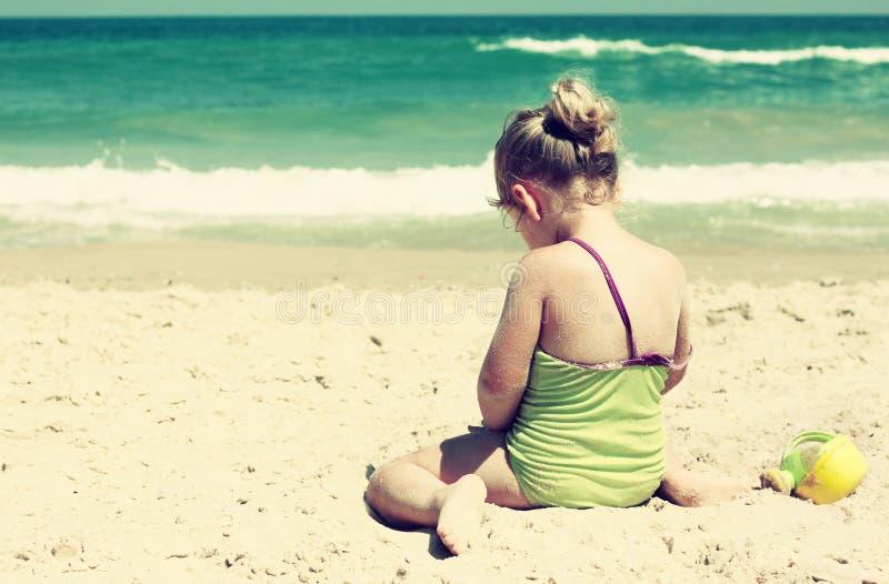 Gullig unge (flicka) som spelar på stranden tonad bild arkivfoto