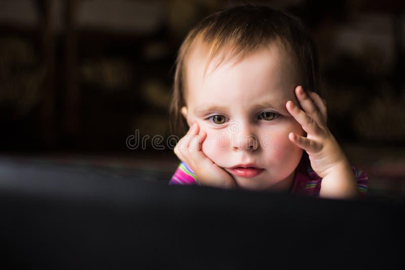 Gullig unge med en bärbar dator. royaltyfri fotografi
