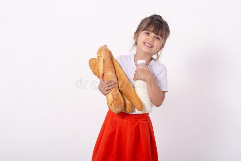 Gullig unge med franskbröd i händerna Bakade nytt bröd och mjölkar, på vit bakgrund Mat för ung familj med ki royaltyfria foton