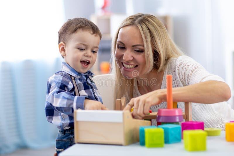 Gullig unge och moder som hemma spelar med leksaker Pys som har rolig tidsfördriv i barnkammare royaltyfria foton