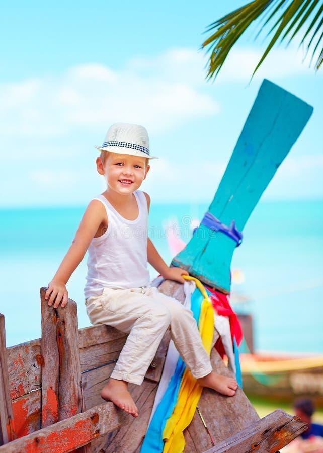 Gullig unge, pojkesammanträde på det gamla fartyget på den tropiska stranden fotografering för bildbyråer