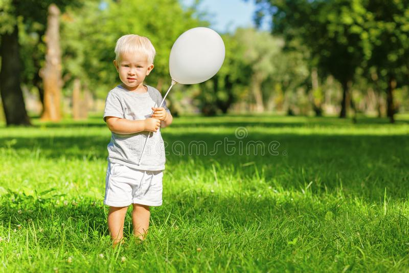 Gullig unge som rymmer en baloon i handen arkivfoton