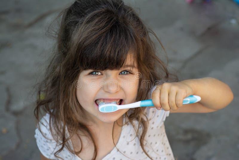 Gullig unge som rymmer en tandborste i hennes hand och borstar tänder arkivfoto