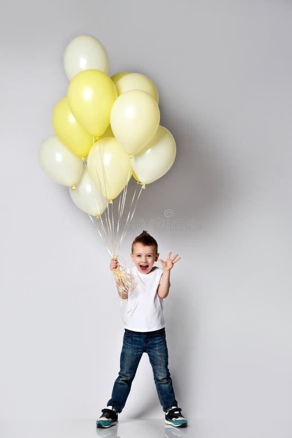 Gullig unge som rymmer m?nga ballonger royaltyfri foto