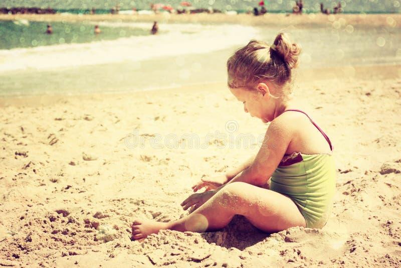 Gullig unge som spelar på stranden filtrerad bild, retro stil royaltyfri bild
