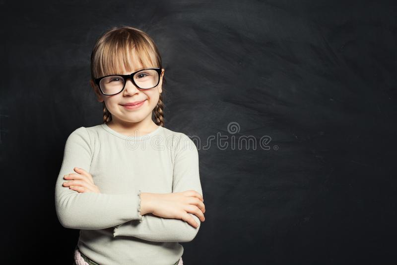 gullig ungestående Lycklig barnflicka som ler och ser kameran på skolaklassrumbakgrund royaltyfri fotografi