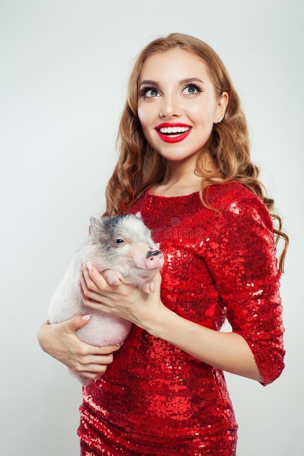 Gullig upphetsad kvinna i den röda trendiga klänningen som rymmer det mini- svinet på vit bakgrund arkivfoton