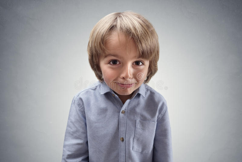 Gullig uppnosig pojke med skyldigt uttryck arkivfoto