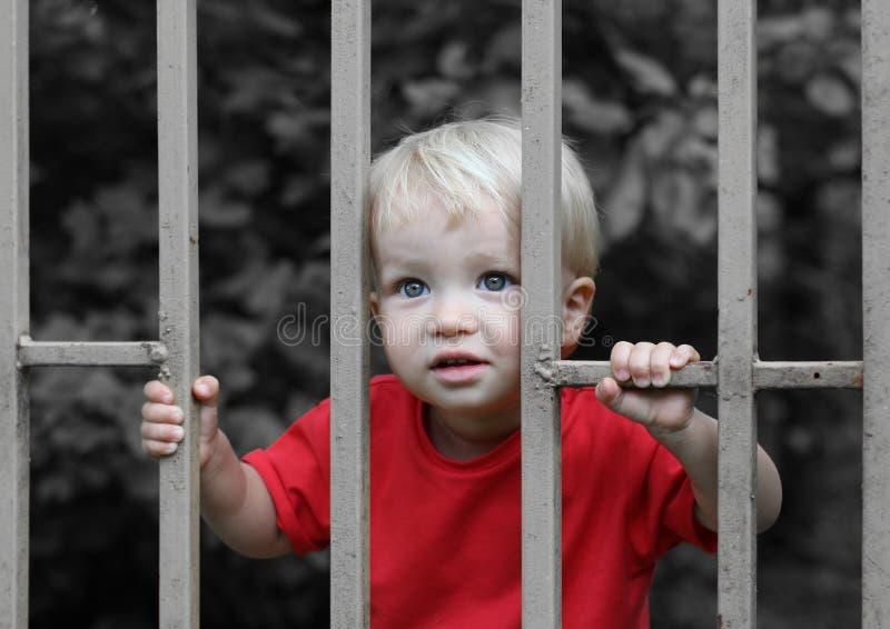 Gullig uppriven blond litet barnpojke bak stänger Barnuppfostransvårigheter eller begrepp för barnslig rättvisa royaltyfria foton