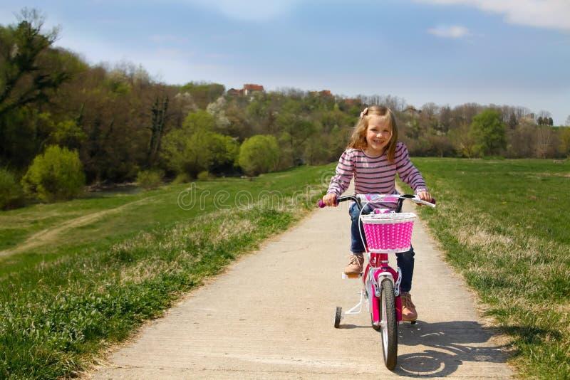 Gullig utomhus- liten flickaridningcykel royaltyfria foton