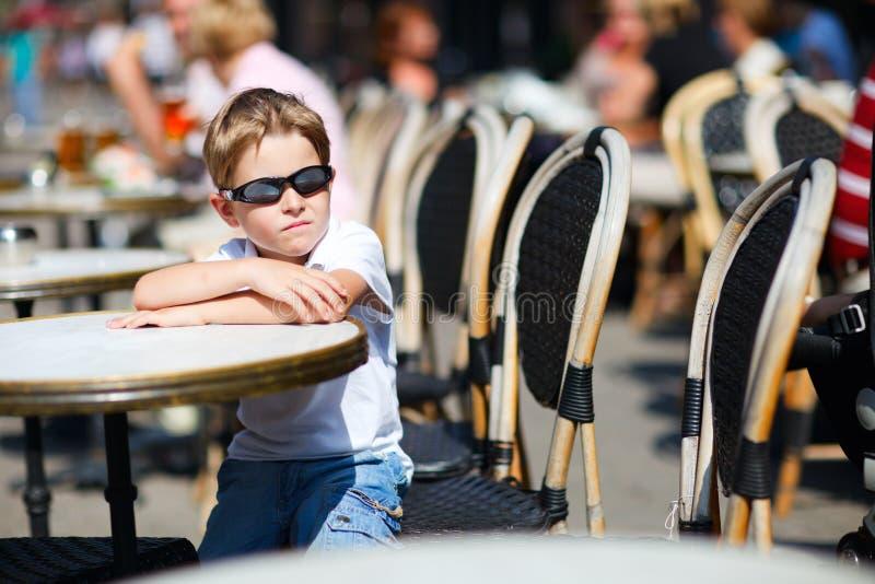 gullig utomhus- sitting för pojkecafe arkivbild