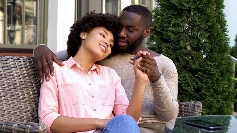 Gulliga afro--amerikan par som kopplar av i utomhus- kafé, kramar och talar, förälskelse fotografering för bildbyråer