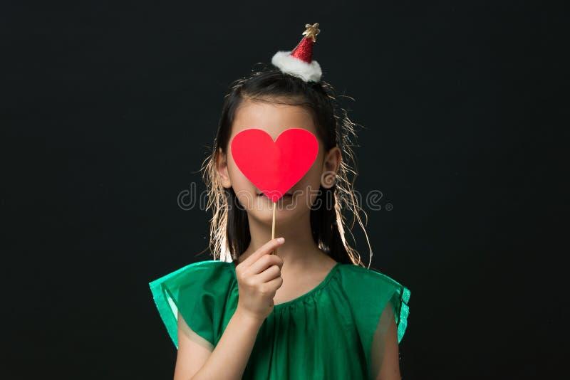 Gulliga asiatiska det iklädda flickabarnet en grön klänning som rymmer en julprydnad, och en hjärta klibbar på en svart bakgrund arkivfoto