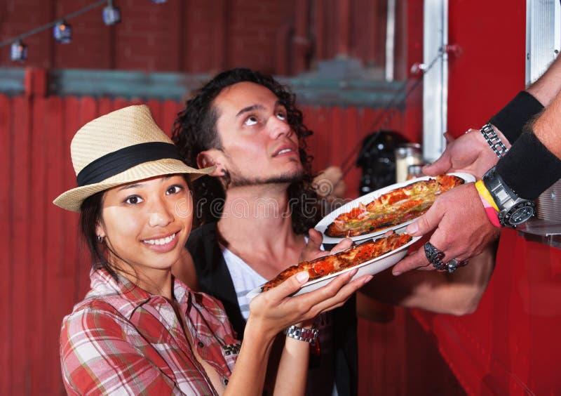 Den gulliga kvinnan med Pizza beställer arkivfoton