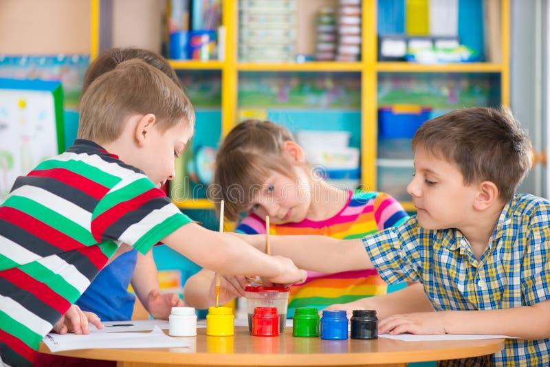 Gulliga barn som drar med färgrika målarfärger på dagiset royaltyfri fotografi