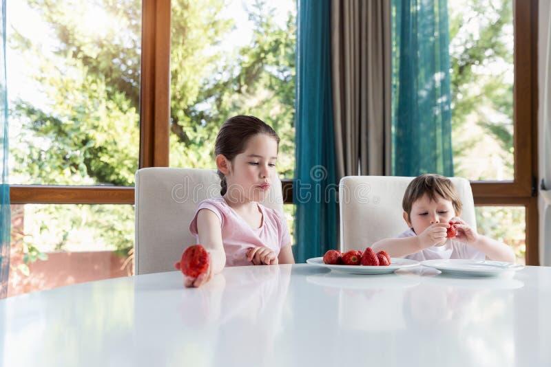 Gulliga barn som hemma ?ter nya mogna jordgubbar royaltyfri foto