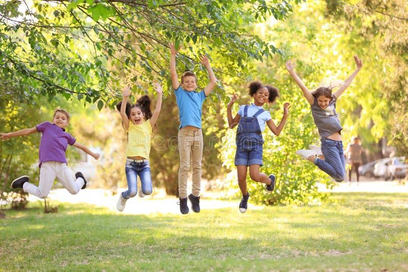 Gulliga barn som tillsammans utomhus spelar på solig dag fotografering för bildbyråer