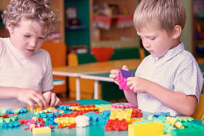 Gulliga caucasian pojkar i en vit skjorta som spelar med färgrika konstruktördetaljer Aktiviteter med barn i dagis fotografering för bildbyråer