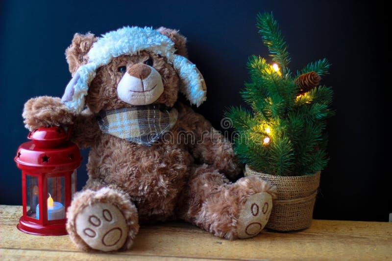 Gulliga den leksakbjörnen som rymmer, tafsar på en röd lykta på en svart bakgrund I ramen kan du se en liten julgran med royaltyfria bilder