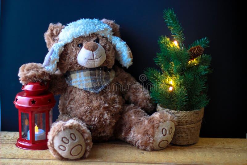 Gulliga den leksakbjörnen som rymmer, tafsar på en röd lykta på en svart bakgrund I ramen kan du se en liten julgran med arkivfoton
