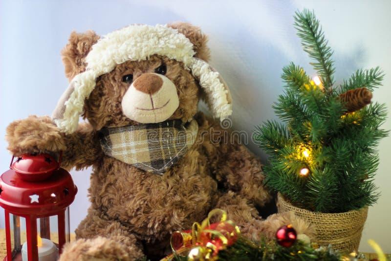 Gulliga den leksakbjörnen som rymmer, tafsar på en röd lykta på en vit bakgrund I ramen kan du se en liten julgran med royaltyfria foton