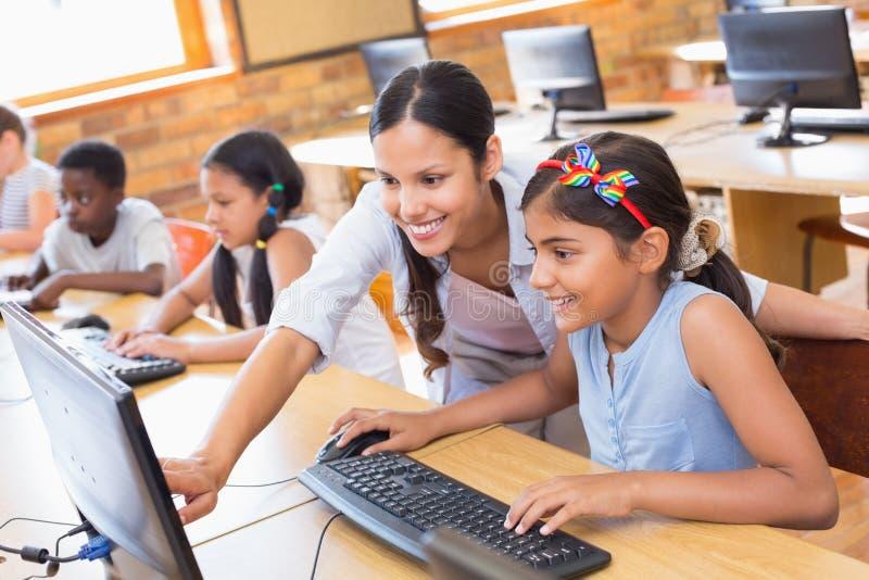 Gulliga elever i datorgrupp med läraren arkivfoto