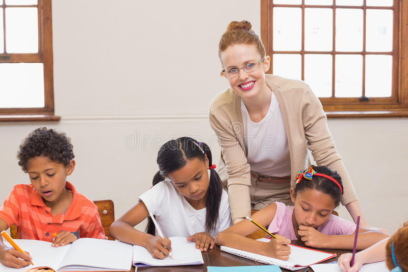 Gulliga elever som får hjälp från lärare i klassrum royaltyfria foton