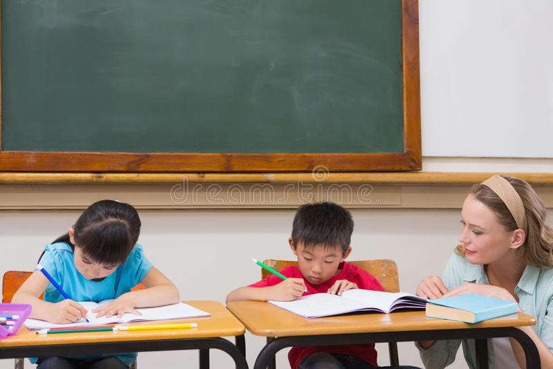 Gulliga elever som får hjälp från lärare i klassrum arkivbild