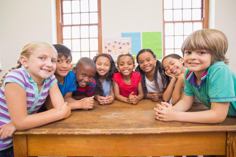 Gulliga elever som ler på kameran i klassrum fotografering för bildbyråer