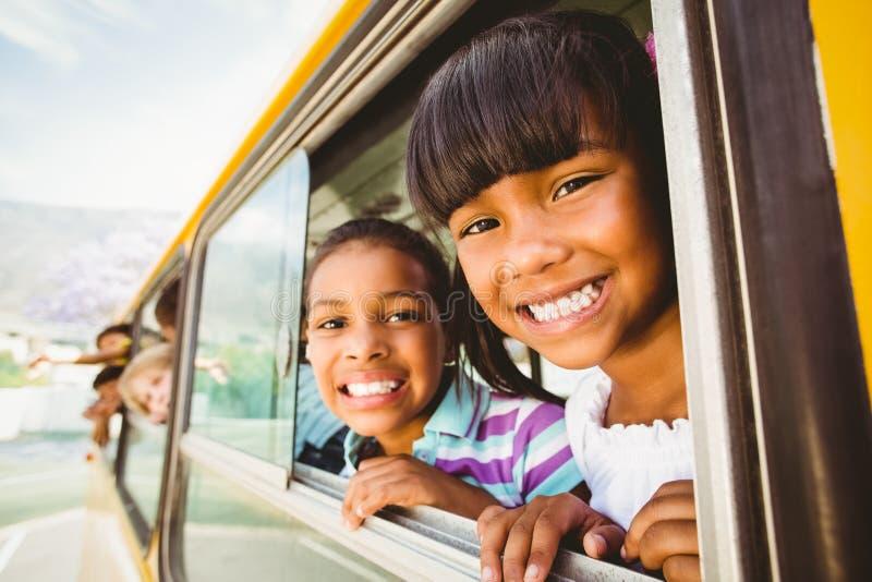 Gulliga elever som ler på kameran i skolbussen royaltyfria bilder