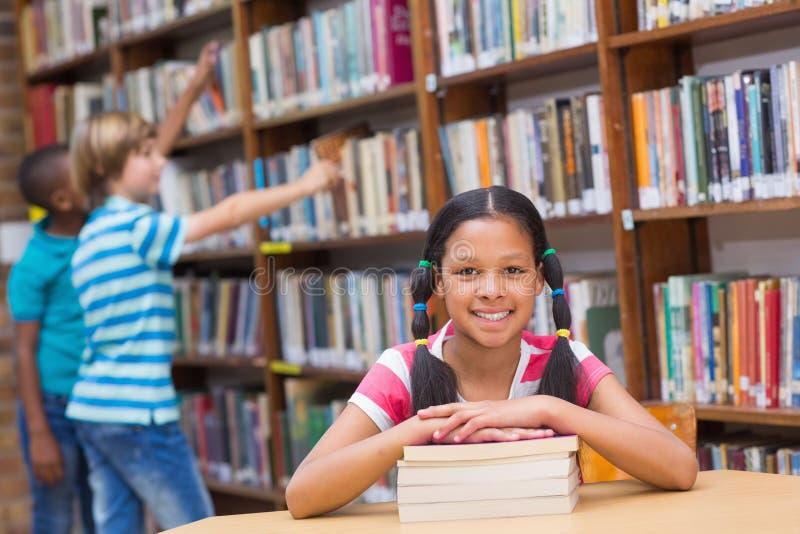 Gulliga elever som söker efter böcker i arkiv arkivbild
