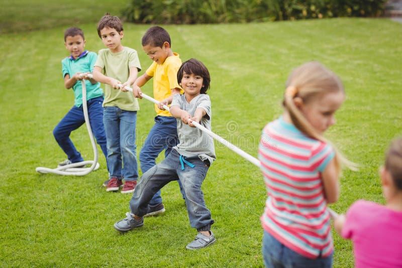 Gulliga elever som spelar dragkampen på gräset utanför arkivfoton