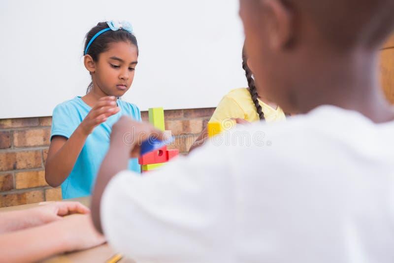 Gulliga elever som spelar med byggnadskvarter royaltyfri fotografi
