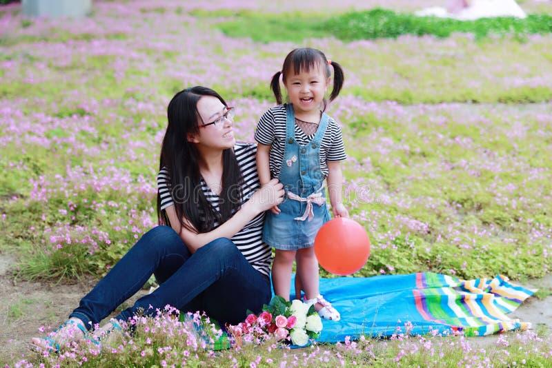 Gulliga förtjusande små behandla som ett barn flickaleendeskratt, och lekballongen har gyckel med modermamman med dottern att tyc royaltyfri bild