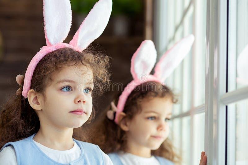 Gulliga flickor för litet barn kopplar samman bärande kaninöron på påskdag Syster som ser fönstret royaltyfria foton