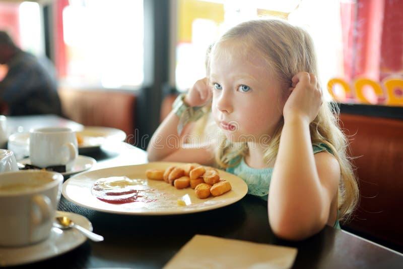 Gulliga flickor som äter ostmassaefterrätten i en restaurang Barn som har sötsaker arkivfoton