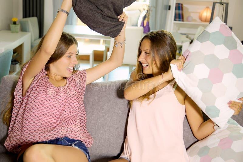 Gulliga flickor som hemma gör att skratta för kuddekamp som är lyckligt royaltyfri foto